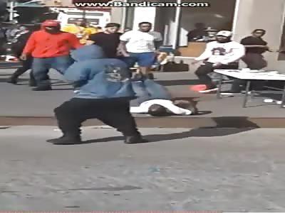 Street vendor beaten by men on the floor in front of his wife and children