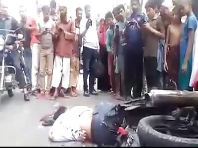 MOTORCYCLIST WITH SPREADED BRAIN ON ASPHALT