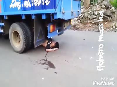 Dead motorcyclist under truck