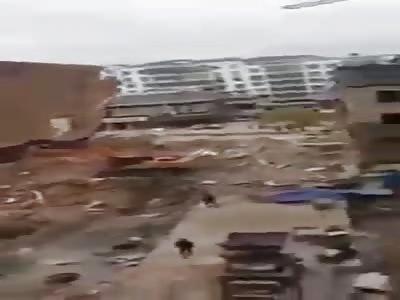 building falls on excavator